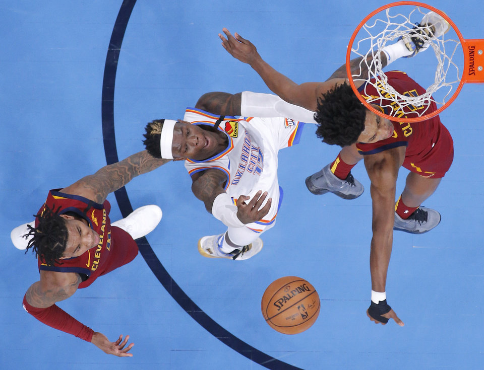 Photo - Oklahoma City's Dennis Schroder (17) is fouled as he goes to the basket between Cleveland's Kevin Porter Jr. (4) and Collin Sexton (2) during an NBA basketball game between the Oklahoma City Thunder and the Cleveland Cavaliers at Chesapeake Energy Arena in Oklahoma City, Wednesday, Feb. 5, 2020. Oklahoma City won 109-103. [Bryan Terry/The Oklahoman]