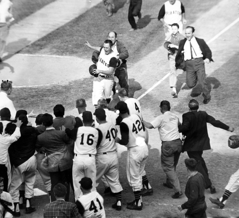Photo - FILE - In this Oct. 13, 1960, file photo, fans rush onto the field toward Pittsburgh Pirates' Bill Mazeroski as he comes home on his Game 7-ending home run in the ninth inning to win the World Series against the New York Yankees in Pittsburgh. Between 1947 and 1962, the Yankees won 10 championships, but Mazeroski and the Pirates stole one away with a wild Game 7 that included in the first ever Series-ending homer. (AP Photo/Harry Harris, File)