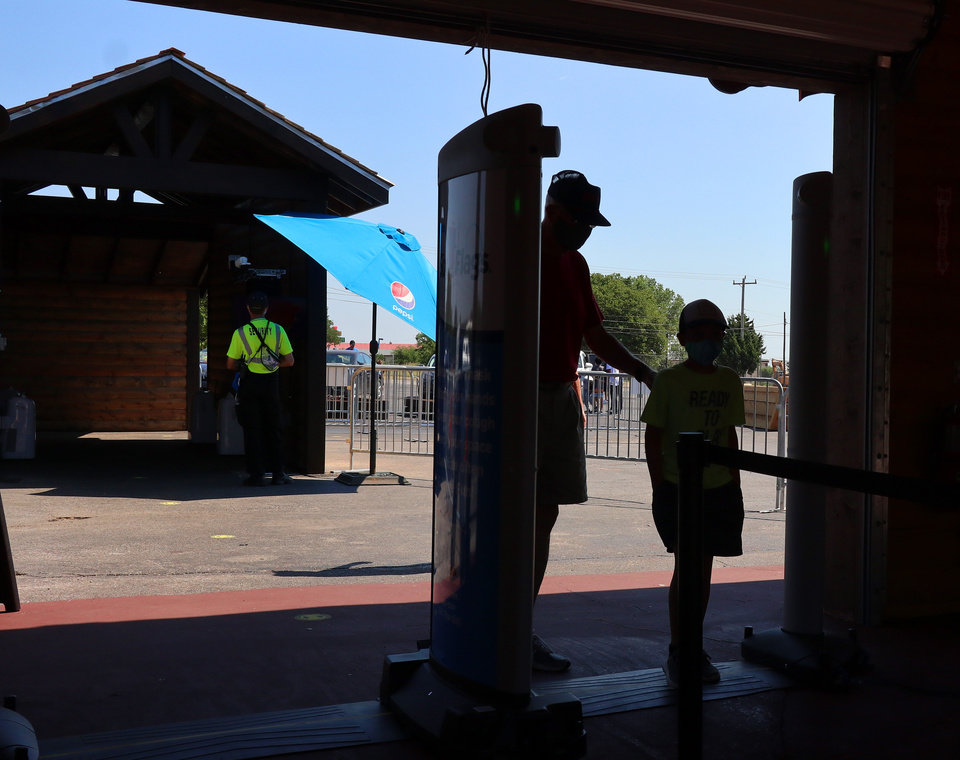 Photo - A man and boy go through the new high tech security system at Frontier City, Wednesday, June 17, 2020. [Doug Hoke/The Oklahoman]