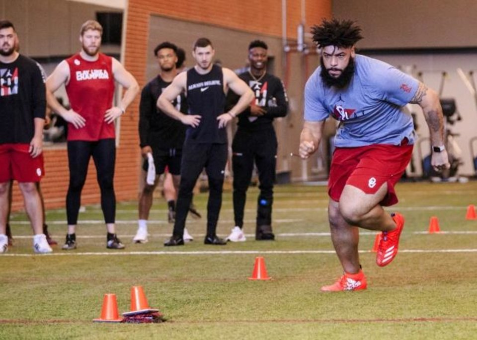 Photo -  Cody Ford runs the shuttle drill as he works out for NFL scouts during the University of Oklahoma football pro day on March 13. [Chris Landsberger/The Oklahoman]