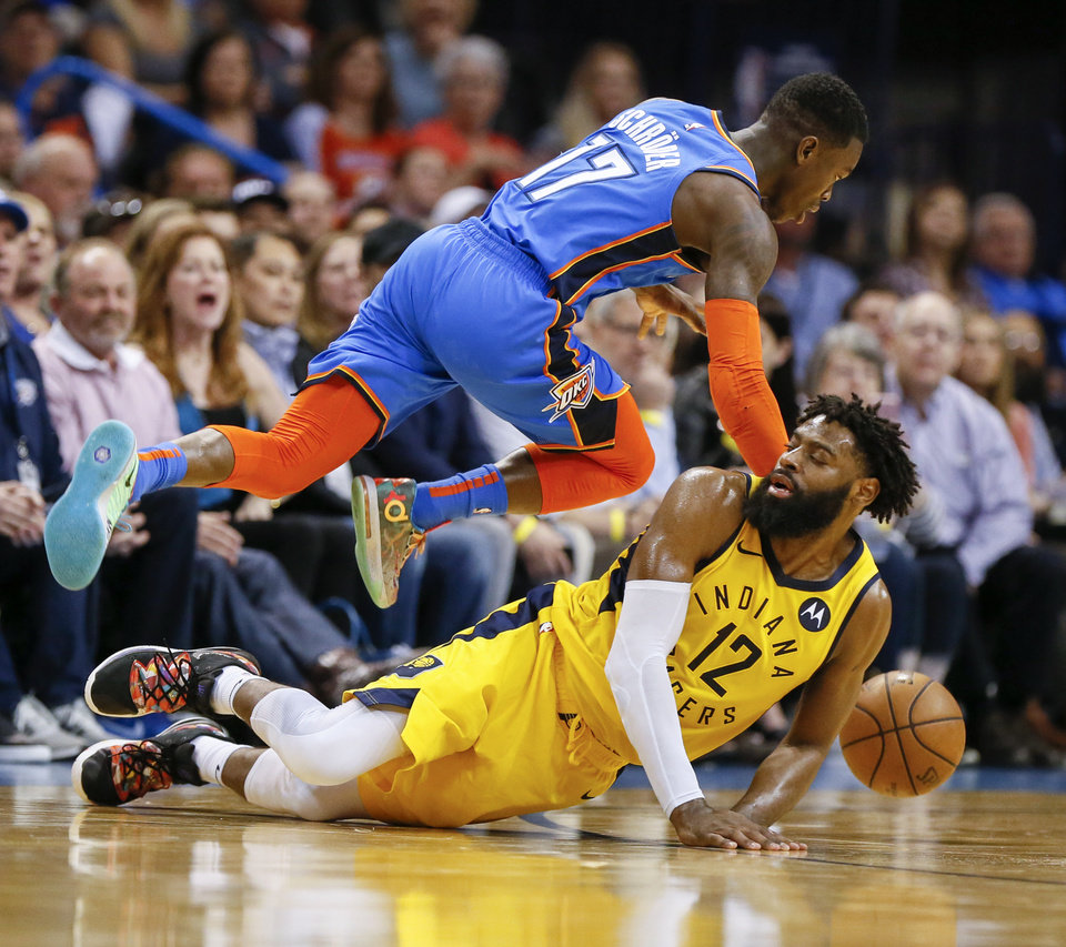 Photo - Oklahoma City's Dennis Schroder (17) leaps over Indiana's Tyreke Evans (12) as he dribbles in the fourth quarter during an NBA basketball game between the Indiana Pacers and the Oklahoma City Thunder at Chesapeake Energy Arena in Oklahoma City, Wednesday, March 27, 2019. Oklahoma City won 107-99. Photo by Nate Billings, The Oklahoman
