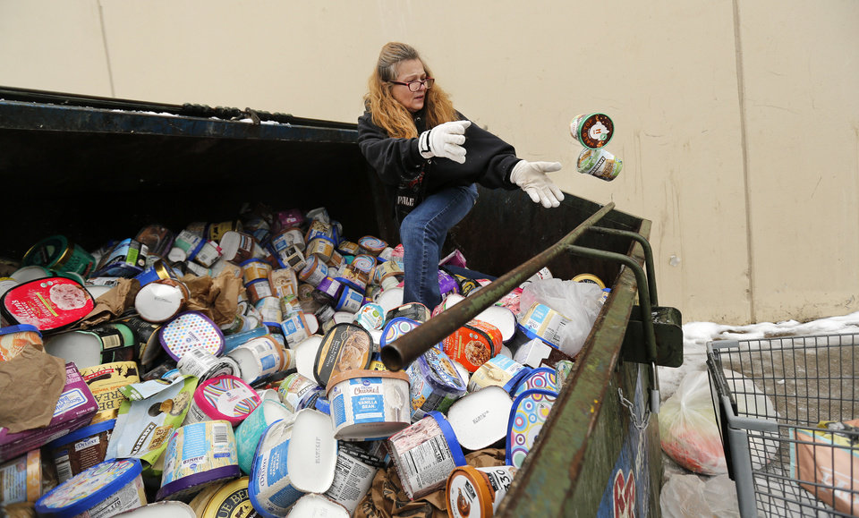 Photo -  FILE - In this Feb. 17, 2021, file photo, LaDonna collects from a trash container ice cream that had been thrown out because of power outages at a Kroger store in Arlington, Texas. LaDonna said she's collecting the frozen goods for her neighbors.