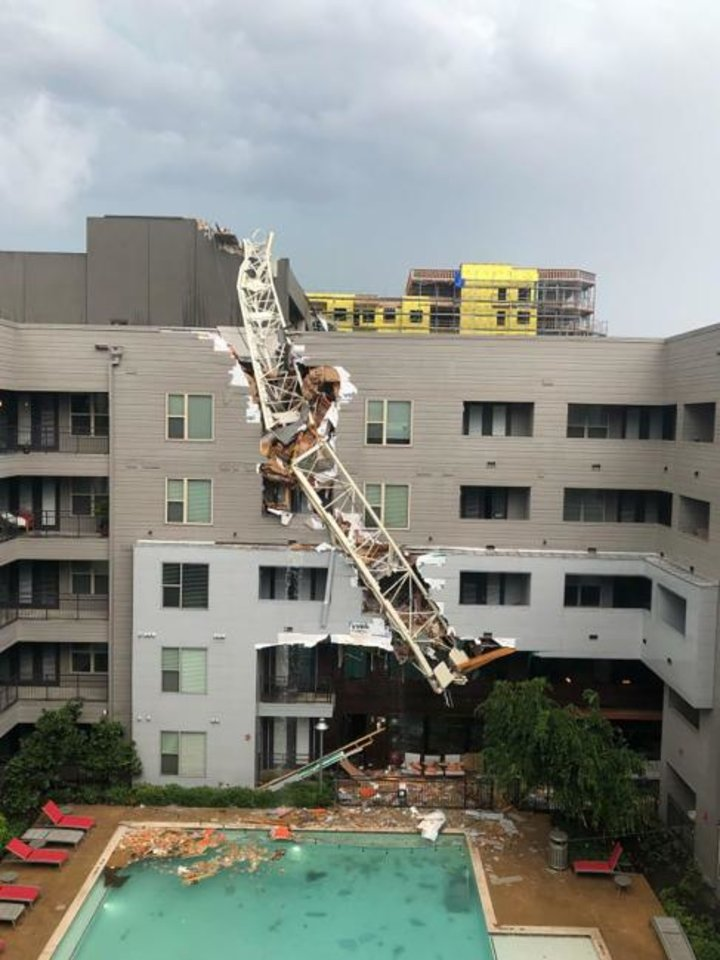 Photo - This photo provided by Michael Santana shows the scene after a crane collapsed into Elan City Lights apartments in Dallas amid severe thunderstorms Sunday, June 9, 2019. (Michael Santana via AP)