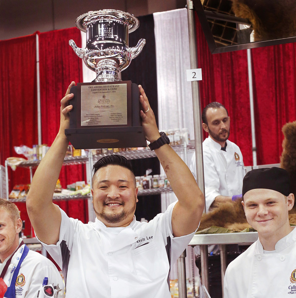 Photo -  Kevin Lee, chef for the winning team, lifts the trophy in a gesture of victory. At right is Chris Gradwohl, a culinary student from Platt College, who was Lee's assistant for the Culinary Cook-off at the Oklahoma Restaurant Association Convention and Expo at Cox Convention Center in downtown Oklahoma City. [Photo by Jim Beckel, The Oklahoman]