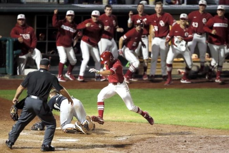Photo -  Oklahoma's Tanner Tredaway scores the game-winning run in the 10th inning Saturday in a 3-2 win against OSU at Bricktown Ballpark. [Bryan Terry/The Oklahoman]