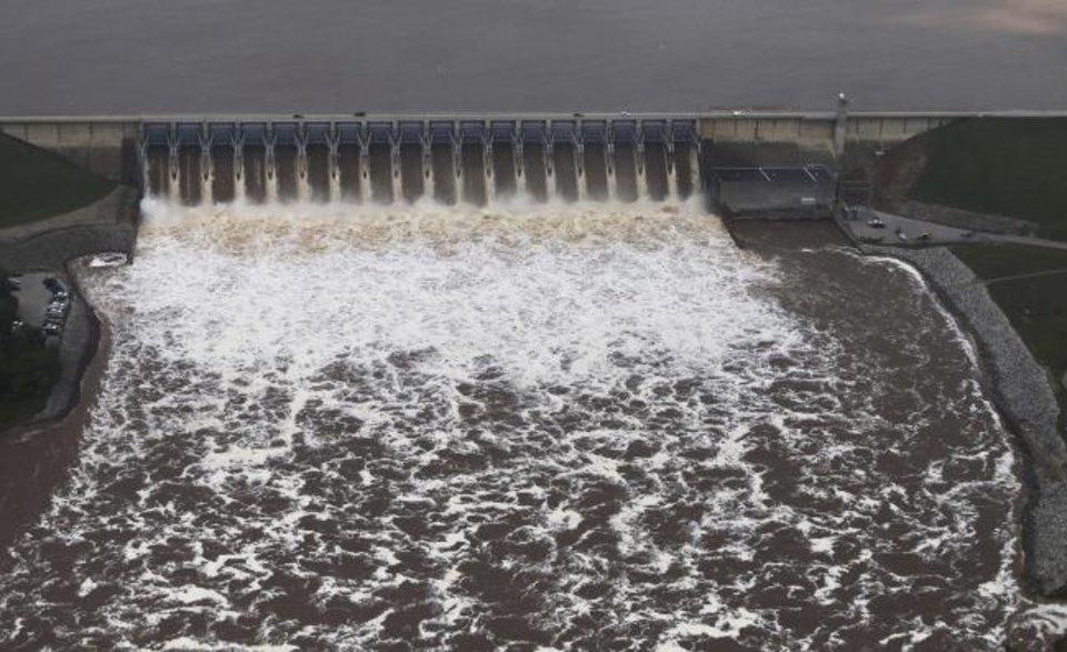 Photo -  Water flows over the Keystone Dam on the Arkansas River on Wednesday. Authorities encouraged people living along the Arkansas River in the Tulsa suburb of Bixby and low-lying areas near creeks both north and south of Okmulgee, about 35 miles south of Tulsa to leave their homes. [Tom Gilbert/Tulsa World]