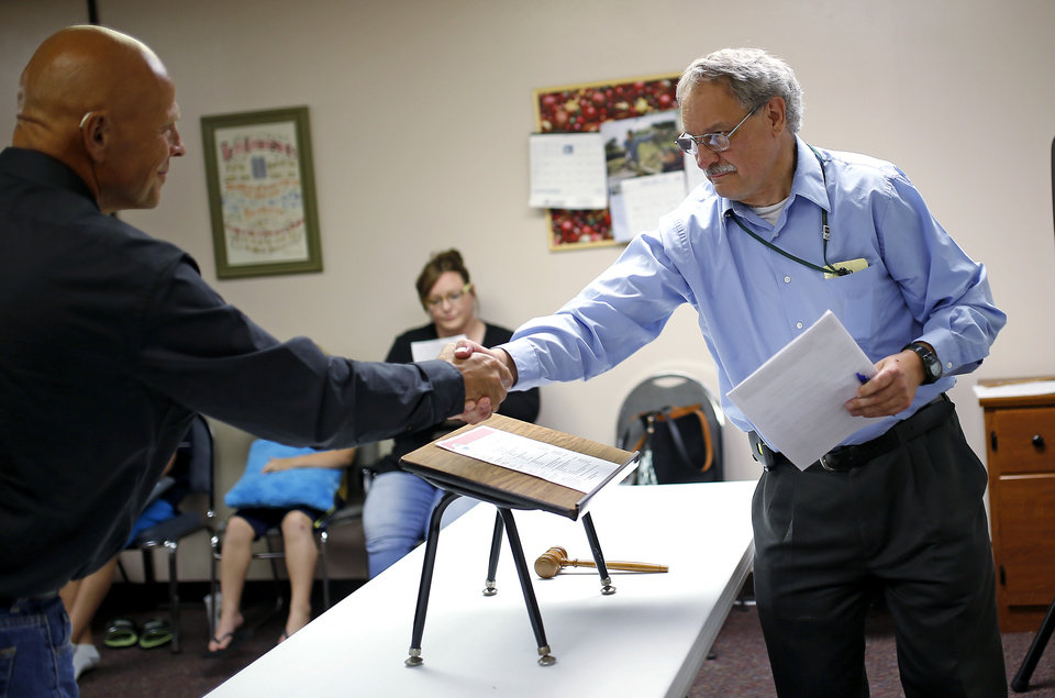 Photo -  Paul Davis, right, shakes hands with Doug Weeks during a Moore Toastmasters meeting. [PHOTO BY BRYAN TERRY, THE OKLAHOMAN]