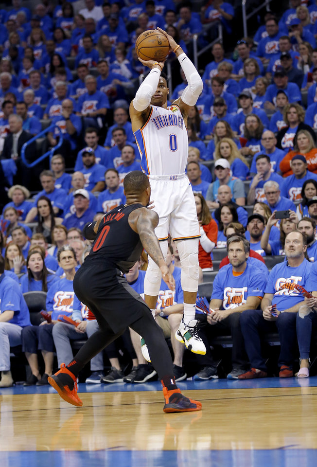 Photo - Oklahoma City's Russell Westbrook (0) shoots a 3-point basket over Portland's Damian Lillard (0) during Game 4 in the first round of the NBA playoffs between the Portland Trail Blazers and the Oklahoma City Thunder at Chesapeake Energy Arena in Oklahoma City, Sunday, April 21, 2019.  Photo by Sarah Phipps, The Oklahoman