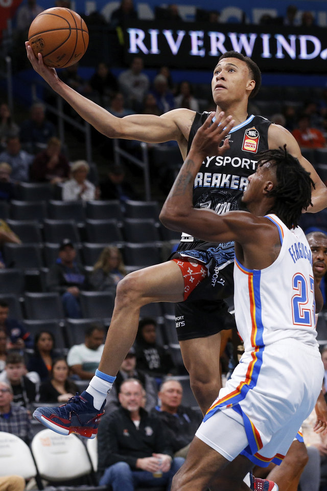 Photo - New Zealand Breakers guard R.J. Hampton, left, goes up for a shot in front of Oklahoma City Thunder guard Terrance Ferguson (23) during the first half of an NBA basketball exhibition game Thursday, Oct. 10, 2019, in Oklahoma City. (AP Photo/Sue Ogrocki)