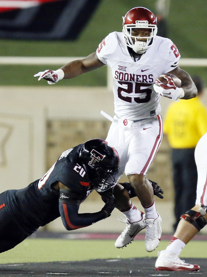 Photo - Texas Tech's Jordyn Brooks (20) tries to stop Oklahoma's Joe Mixon (25) in the first quarter during a college football game between the University of Oklahoma Sooners (OU) and Texas Tech Red Raiders at Jones AT&T Stadium in Lubbock, Texas, Saturday, Oct. 22, 2016. Photo by Nate Billings, The Oklahoman