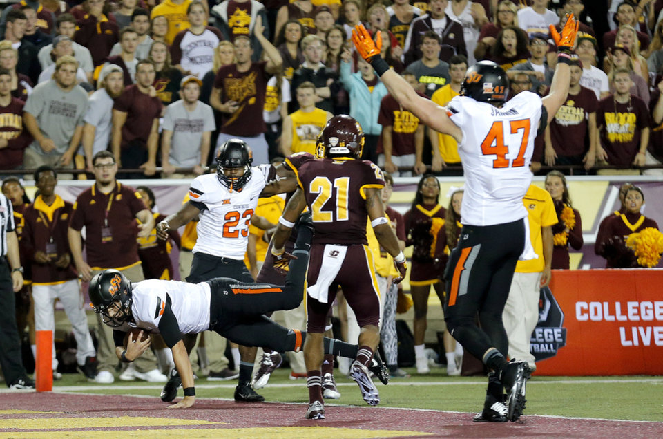 Photo - Oklahoma State's Mason Rudolph (2) dives in for a touchdown during the college football game between the Central Michigan Chippewas and the Oklahoma State University Cowboys at the Kelly-Shorts Stadium in Mount Pleasant, Mich., Thursday, Sept. 3, 2015. Photo by Sarah Phipps, The Oklahoman