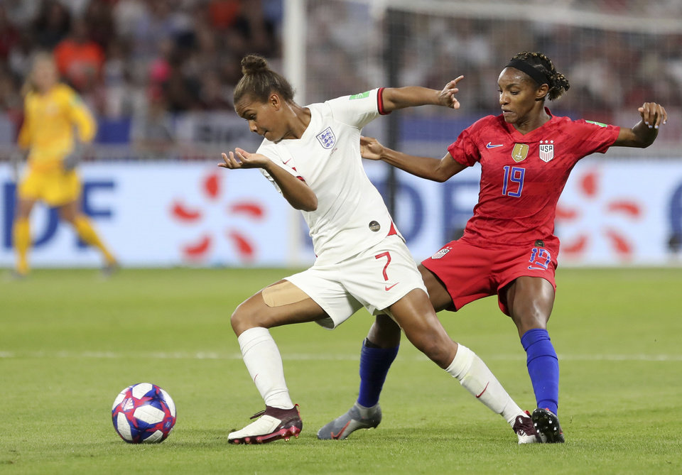 Photo - England's Nikita Parris, left, and United States' Crystal Dunn challenge for the ball during the Women's World Cup semifinal soccer match between England and the United States, at the Stade de Lyon outside Lyon, France, Tuesday, July 2, 2019. (AP Photo/Laurent Cipriani)
