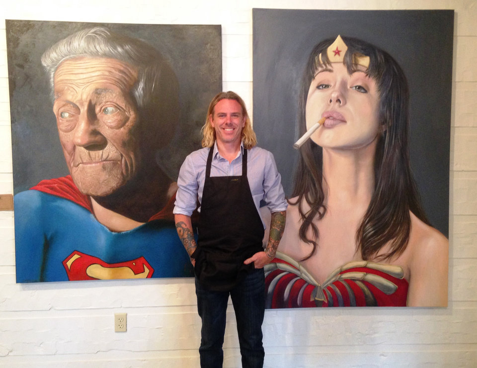 Photo -  Edmond artist Reian Williams poses with his paintings,