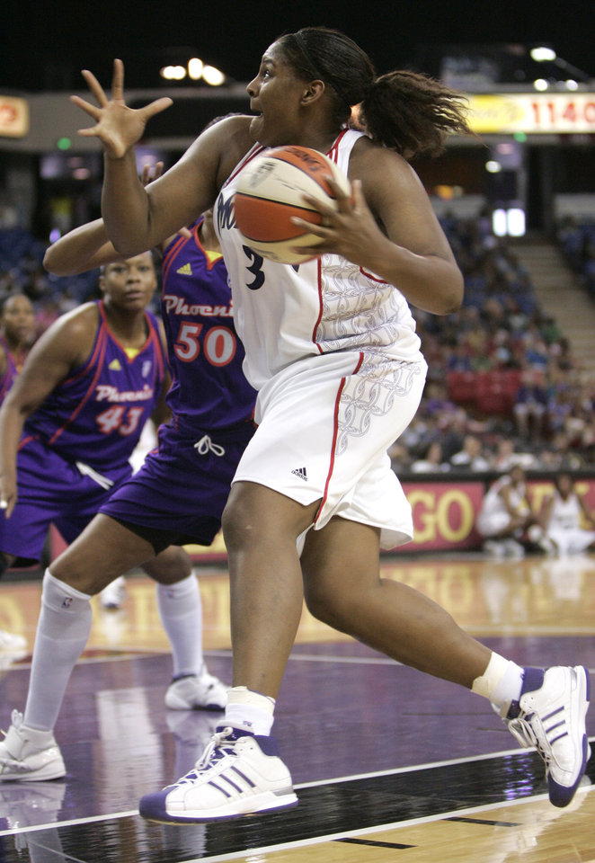 Photo - Sacramento Monarchs rookie center Courtney Paris, right, drives to the basket against Phoenix Mercury center Tangela Smith, left, during the second quarter of a preseason WNBA basketball game in Sacramento, Calif., Wednesday, May 27, 2009. (AP Photo/Rich Pedroncelli) ORG XMIT: SCA103