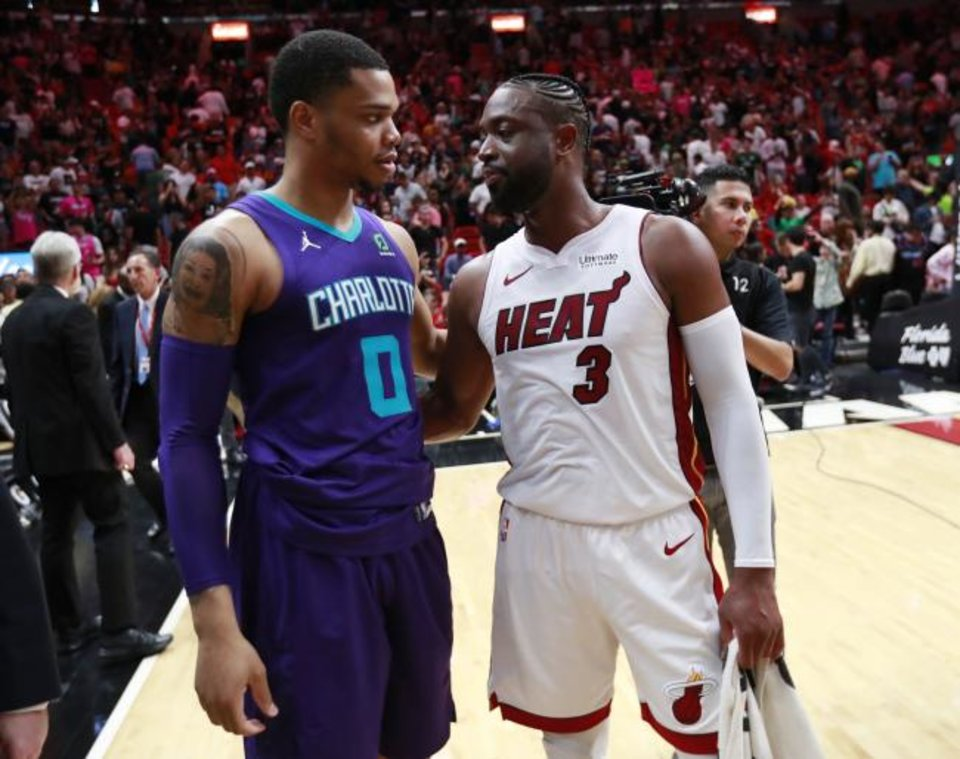 Photo -  Miami Heat guard Dwyane Wade (3) talks with Charlotte Hornets forward Miles Bridges (0) after Sunday's game in Miami. [AP Photo/Wilfredo Lee]