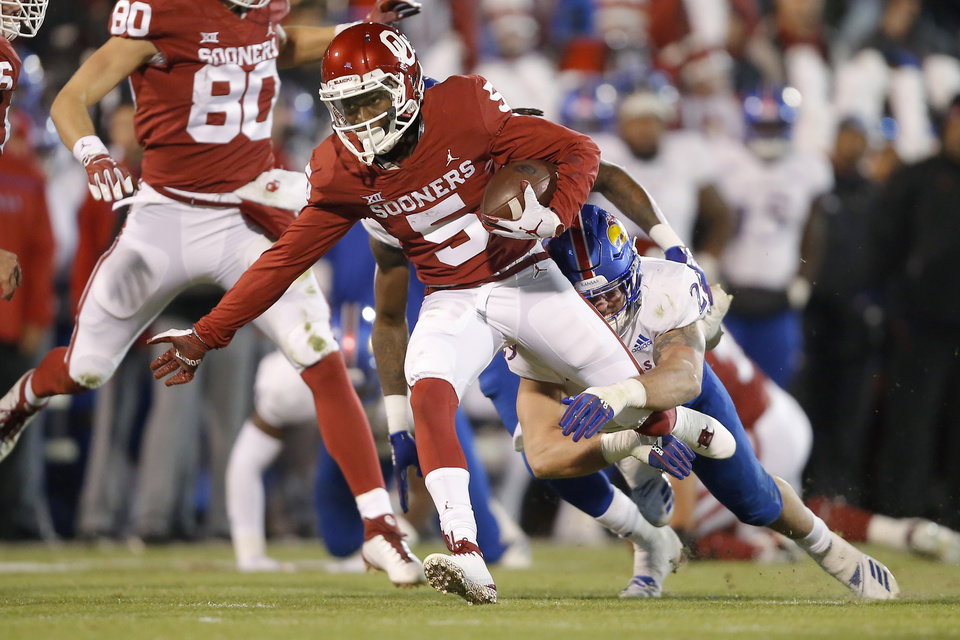Photo - Oklahoma's Marquise Brown (5) is brought down by Kansas' Joe Dineen Jr. (29) during a college football game between the University of Oklahoma Sooners (OU) and the Kansas Jayhawks (KU) at Gaylord Family-Oklahoma Memorial Stadium in Norman, Okla., Saturday, Nov. 17, 2018. Photo by Bryan Terry, The Oklahoman