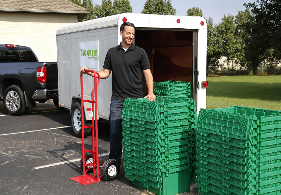 Photo -  Big Green Moving Boxes co-owner Steven Embree stands by some of the moving boxes available for rent in the Oklahoma City area. Embree's business rents stackable, reusable boxes for private and commercial moves.