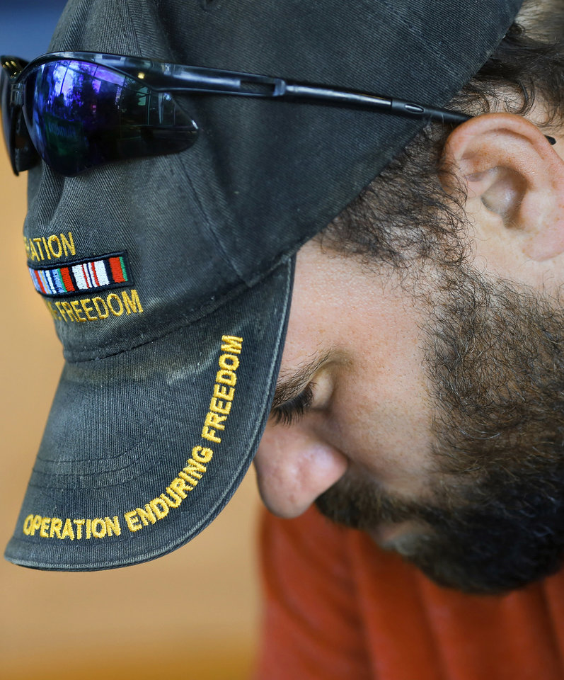 Photo -  Marine veteran Kye Tuepkes wears an Operation Enduring Freedom hat while he completes paperwork during his visit to the Sooner Stand Down for homeless veterans on Friday at the Homeless Alliance's WestTown Homeless Resource Campus in Oklahoma City. [Photo by Jim Beckel, The Oklahoman]