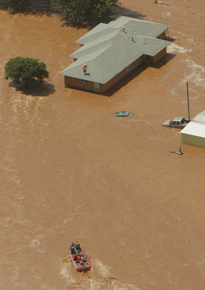 Photo - Flooding in Kingfisher after tropical storm Erin hit the area early Sunday, Aug. 19, 2007. Rescuers in a boat go to rescue a man on a house. BY MATT STRASEN, THE OKLAHOMAN/KWTV SKYNEWS 9