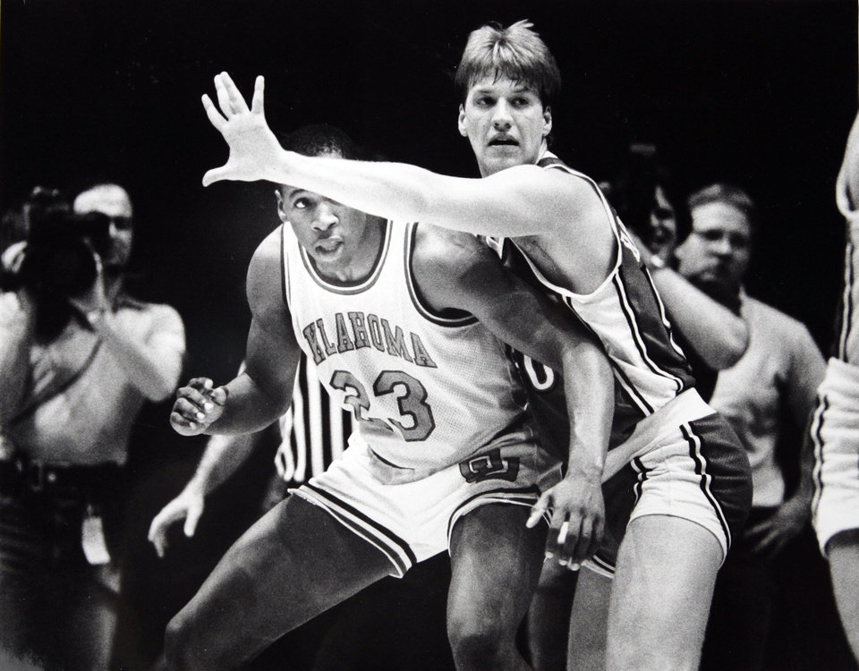 Photo - Former OU basketball player Wayman Tisdale. Wayman Tisdale peeks under the arm of Paul Brozovich, one of three Rebels who fouled out. 3-4-84 ORG XMIT: KOD