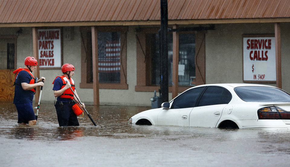 Photo - A pair of Oklahoma City firefighters walks through deep water on SW 29 Street to check a submerged car for trapped occupants after heavy rains overwhelmed stormwater drainage systems and flooded streets, requiring  high water rescues in Oklahoma City as another round of severe storms passes through the metro. No one was in the vehicle. The National Weather Service reports up to 1.5 inches of rain fell during a 30-minute period Thursday, June 6, 2019,  in the western part of the Oklahoma City area.  Firefighters said they assisted four people to safety between 11 o'clock and noon in the deep water that flooded this intersection at SW 29 and May.  [Jim Beckel/The Oklahoman]