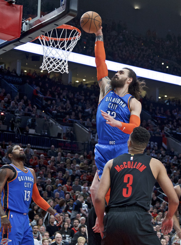 Photo - Oklahoma City Thunder center Steven Adams, center, dunks over Portland Trail Blazers guard CJ McCollum, right, during the first half of an NBA basketball game in Portland, Ore., Thursday, March 7, 2019. (AP Photo/Craig Mitchelldyer)