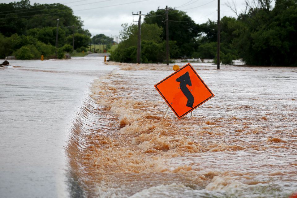 Photo - Floodwaters rush over NW 206 just west of Portland in Oklahoma City, Tuesday, May 21, 2019. [Bryan Terry/The Oklahoman]