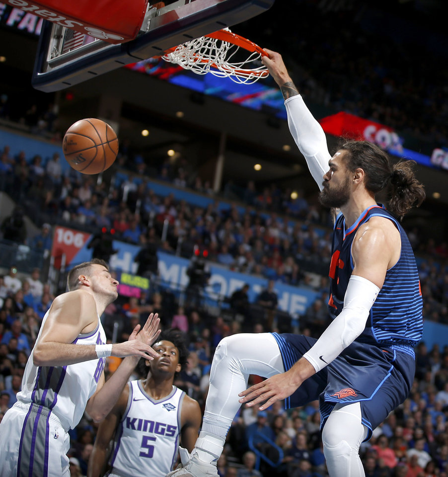 Photo - Oklahoma City's Steven Adams (12) dunks the ball beside Sacramento's Nemanja Bjelica (88) an De'Aaron Fox during an NBA basketball game between the Oklahoma City Thunder and the Sacramento Kings at Chesapeake Energy Arena in Oklahoma City, Sunday, Oct. 21, 2018. Photo by Bryan Terry, The Oklahoman