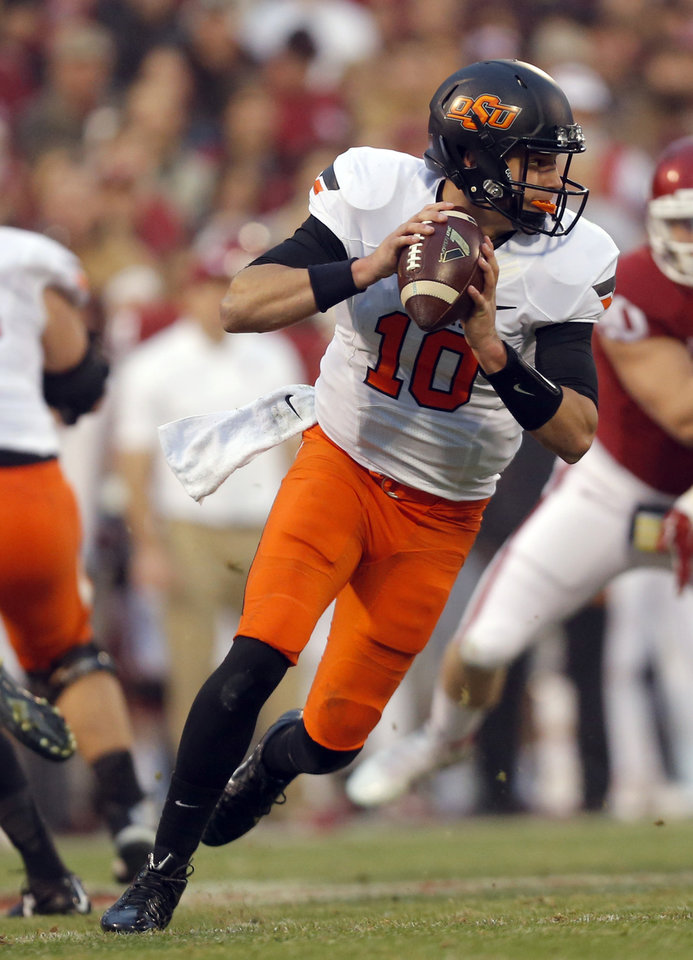 Photo - Oklahoma State's Mason Rudolph (10) looks to pass during the Bedlam college football game between the University of Oklahoma Sooners (OU) and the Oklahoma State Cowboys (OSU) at Gaylord Family-Oklahoma Memorial Stadium in Norman, Okla., Saturday, Dec. 6, 2014. Photo by Sarah Phipps, The Oklahoman