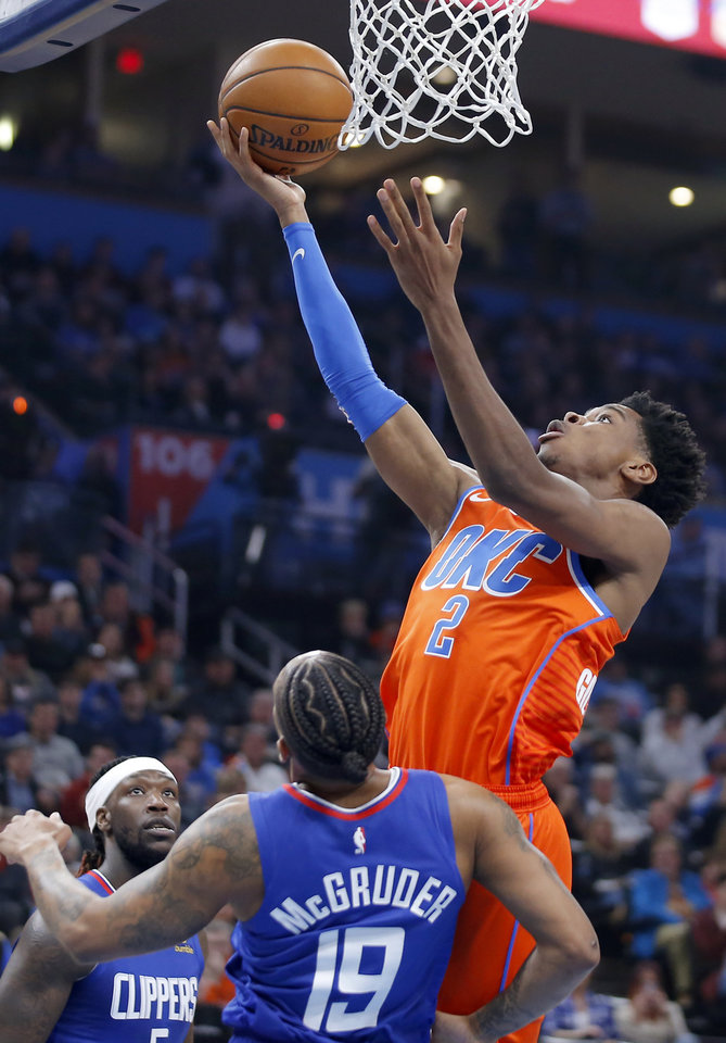 Photo - Oklahoma City's Shai Gilgeous-Alexander (2) puts up a shot over LA's Rodney McGruder (19) during an NBA basketball game between the Oklahoma City Thunder and the LA Clippers at Chesapeake Energy Arena in Oklahoma City, Sunday, Dec. 22, 2019. Oklahoma City won 118-112. [Bryan Terry/The Oklahoman]