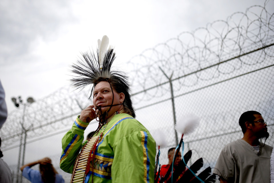 Photo - Inmate Michael Benham, a Choctaw, walks near the fence during the 27th Annual Confined Inter-Tribal Group Gourd Dance & Pow-Wow inside Joseph Harp Correctional Center in Lexington, Okla., on Friday, September 9, 2016. Photo by Bryan Terry, The Oklahoman