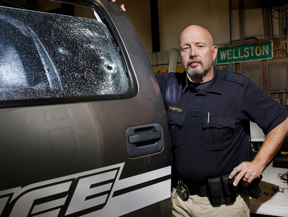 Photo -  Wellston police officer Jim Hampton shows a large bullet hole in the window of fellow officer Shawn Stewart's patrol vehicle. Hampton is back on duty and Stewart continues to recover from his wounds a month after a shoot-out and an ensuing crime spree prompted a statewide manhunt that ended with the suspect being killed. [Photo by Jim Beckel, The Oklahoman]