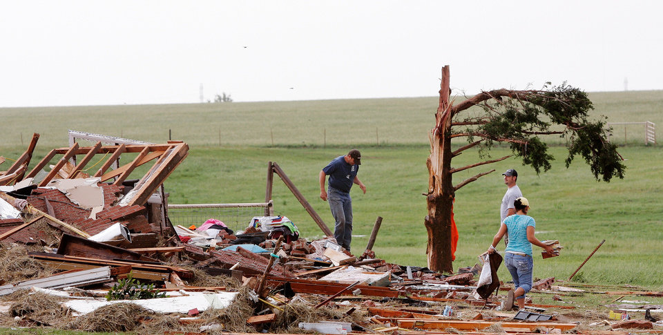 Photo - Kiley Witte, 34, left, is joined by two friends walking the rubble of his home on SH 74 east of Cashion after a tornado destroyed it  Tuesday afternoon,  May 24, 2011,   Witte and his dog were in a storm cellar in his front yard.  His wife and young son had done to Oklahoma City and were in a safe room of a business where she works.  Photo by Jim Beckel, The Oklahoman