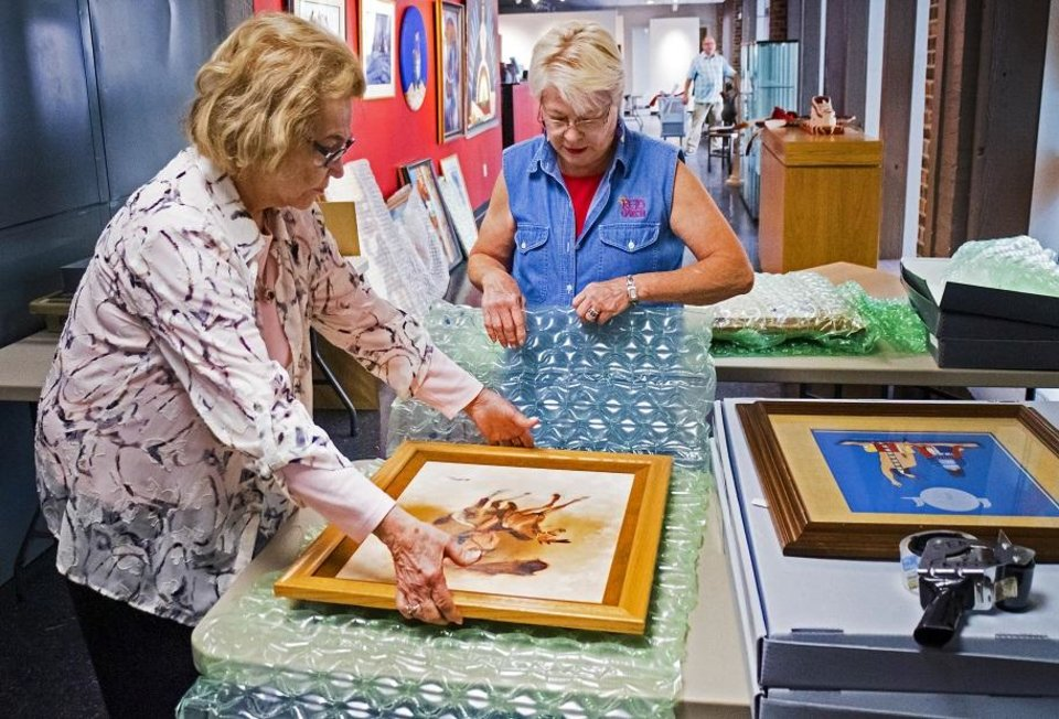 Photo - Lou Kerr and Teri Stanek, from left, work to pack artwork at the Red Earth Art Center in Oklahoma City, Okla. on Thursday, May 16, 2019. The center is relocating to ground floor of BancFirst Tower. [Chris Landsberger/The Oklahoman]