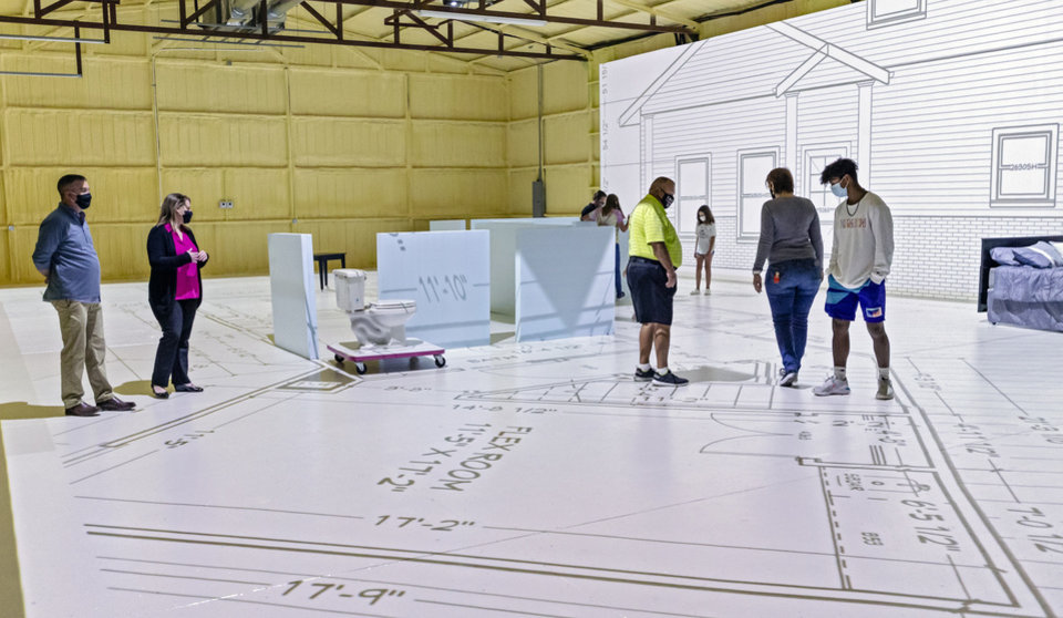 Photo - Projected Plans owners Brian and Angela Porch, left, assist clients as they experience the layout of their new home with projected life size blueprints at Projected Plans in Norman, Okla. on Tuesday, Sept. 29, 2020.  [Chris Landsberger/The Oklahoman]