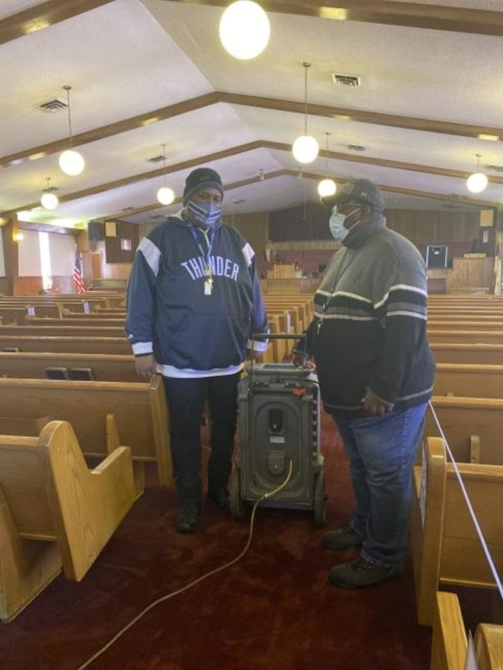 Photo -  Larry Thompson and the Rev. James Harris Jr., talk in the newer sanctuary at Antioch Institutional Baptist Church, 507 N Bath Circle, which experienced water damage from burst water pipes. [Carla Hinton/The Oklahoman]