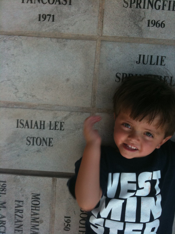 Photo - Jackson Stone, now 6, lies next to a memorial stone for his brother, Isaiah Lee Stone, at the University of Oklahoma Memorial Student Union. Isaiah died from complications of pediatric epilepsy at the age of 11 months. HIs parents, C. Renzi and Lee Anne Stone have begun the Isaiah Stone Pediatric Epilepsy Lecture Series to raise money and awareness of the need for more research, specialists and treatment options for children with epilepsy. Photo provided.