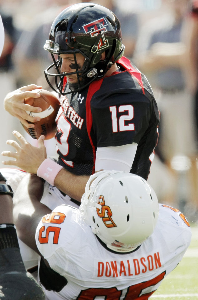Photo - Texas Tech quarterback Taylor Potts (12) is sacked by OSU's Chris Donaldson (95) in the first quarter during the college football game between the Oklahoma State University Cowboys and Texas Tech University Red Raiders at Jones AT&T Stadium in Lubbock, Texas, Saturday, October 16, 2010. Photo by Nate Billings, The Oklahoman