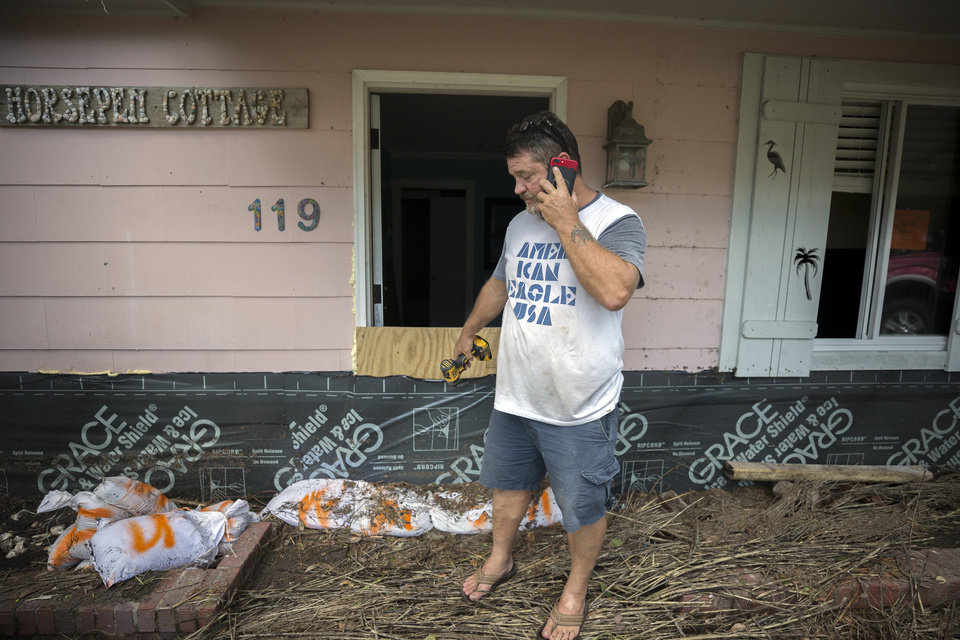 Photo - Joey Spalding talks with friends on his cellphone, Tuesday, Sept., 12, 2017, on Tybee Island, Ga., while cleaning up after Tropical Storm Irma flooded his neighborhood yesterday. (AP Photo/Stephen B. Morton)