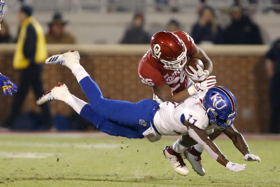 Photo - Oklahoma's Kennedy Brooks (26) is brought down by Kansas' Mike Lee (11) during a college football game between the University of Oklahoma Sooners (OU) and the Kansas Jayhawks (KU) at Gaylord Family-Oklahoma Memorial Stadium in Norman, Okla., Saturday, Nov. 17, 2018. Photo by Bryan Terry, The Oklahoman