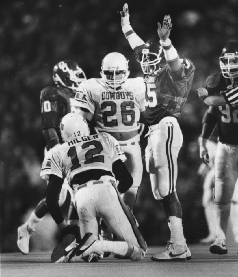 "Photo - FOOTBALL OU UNIVERSITY OF OKLAHOMA 1984 34: Caption reads ""Oklahoma's Tony Rayburn exults over fallen Oklahoma State quarterback Rusty Hilger (12) after a sack late in Saturday's game."" Photo taken by Doug Hoke. Photo taken 11-24-1984. Photo was  published in The Daily Oklahoman 11-26-1984."