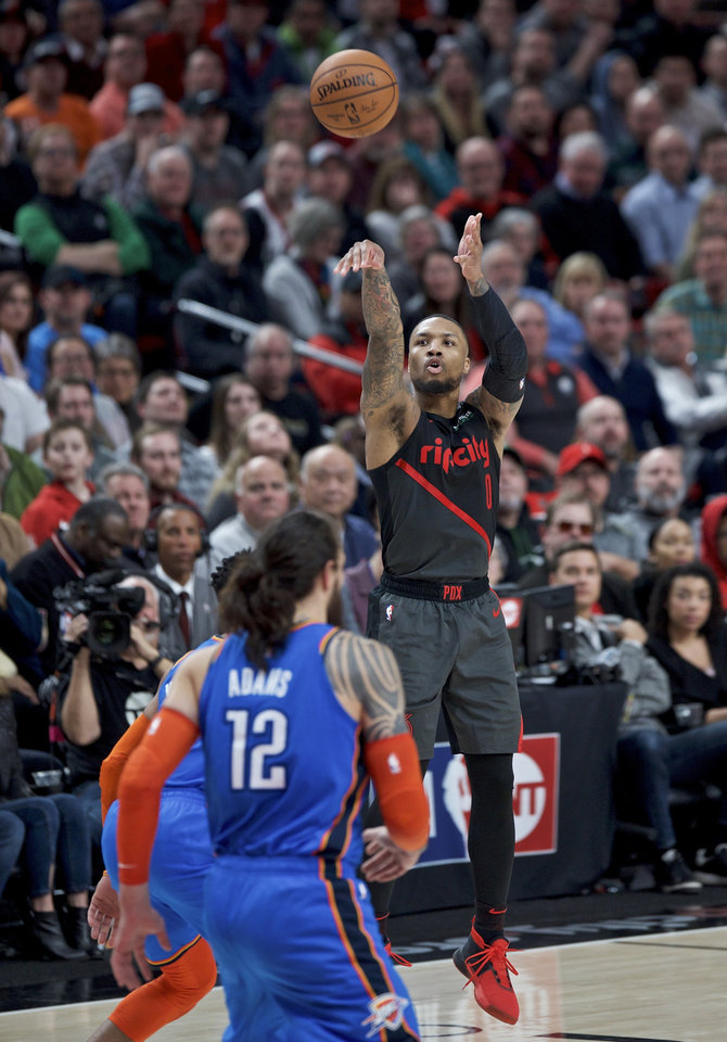 Photo - Portland Trail Blazers guard Damian Lillard, right, shoots over Oklahoma City Thunder center Steven Adams during the second half of an NBA basketball game in Portland, Ore., Thursday, March 7, 2019. The Thunder won 129-121. (AP Photo/Craig Mitchelldyer)