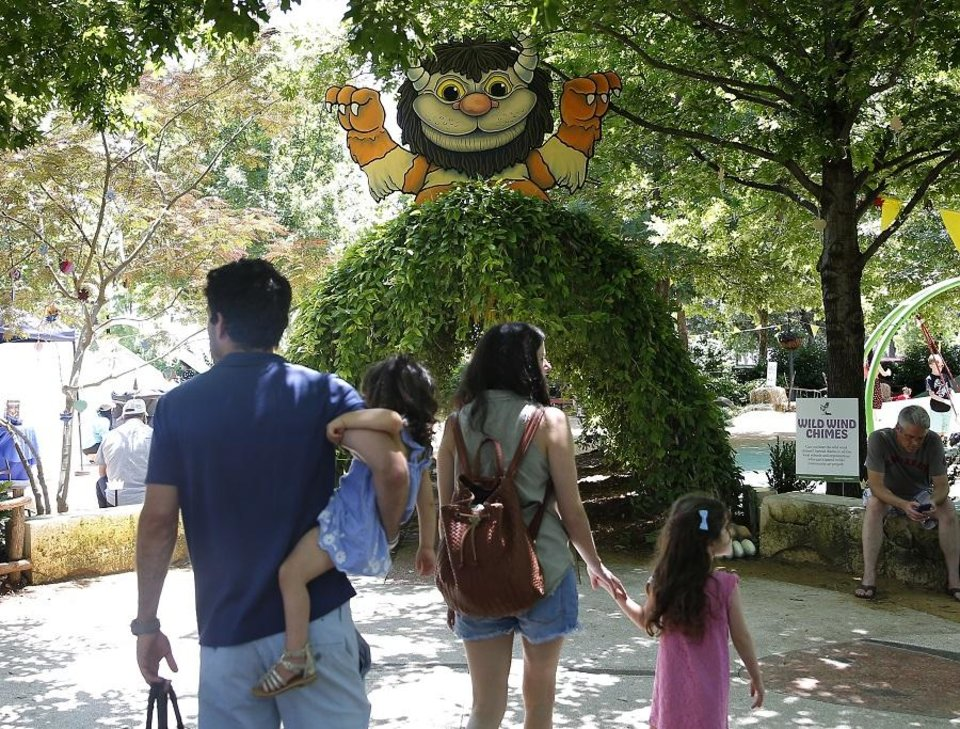 Photo - A family walks in into The Children's Garden, which is decorated as