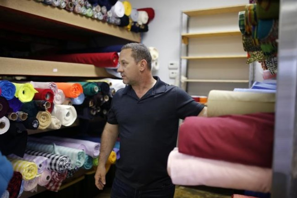 Photo -  Dragos Sescu helps answer customers' questions about fabrics at the OKC Fabric Market. [SARAH PHIPPS/THE OKLAHOMAN]