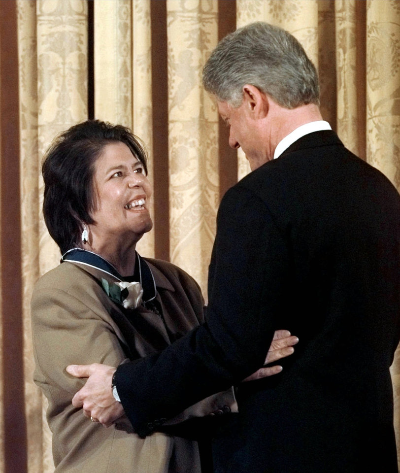 Photo - DEATH: President Bill Clinton embraces Wilma Mankiller after presenting her with a Presidential Medal of Freedom during a ceremony at the White House Thursday Jan. 15,1998. Mankiller received the medal for her work in becoming a strong and creative leader of the Cherokee Nation. Mankiller died Tuesday April 6, 2010 after battling pancreatic cancer. She was 64. (AP Photo/Dennis Cook)