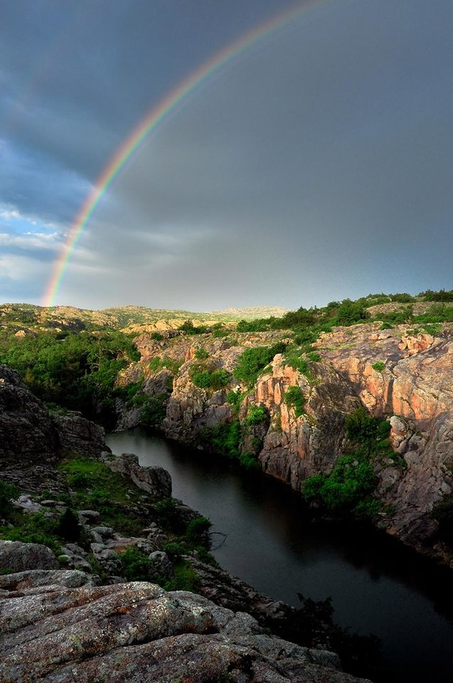 Photo -  A rainbow above Quanah Creek below the Quanah Parker Lake Dam in the Wichita Mountains Wildlife Refuge in southwest Oklahoma. The refuge is an ideal place for nature and wildlife photography. [PHOTO BY MICHAEL DUNCAN]