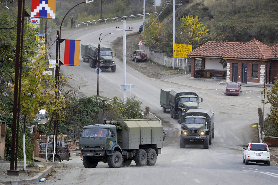 Photo -  In this Sunday photo, a Russian peacekeepers' convoy drives through a street in Stepanakert, the separatist region of Nagorno-Karabakh. [Sergei Grits/the associated press]