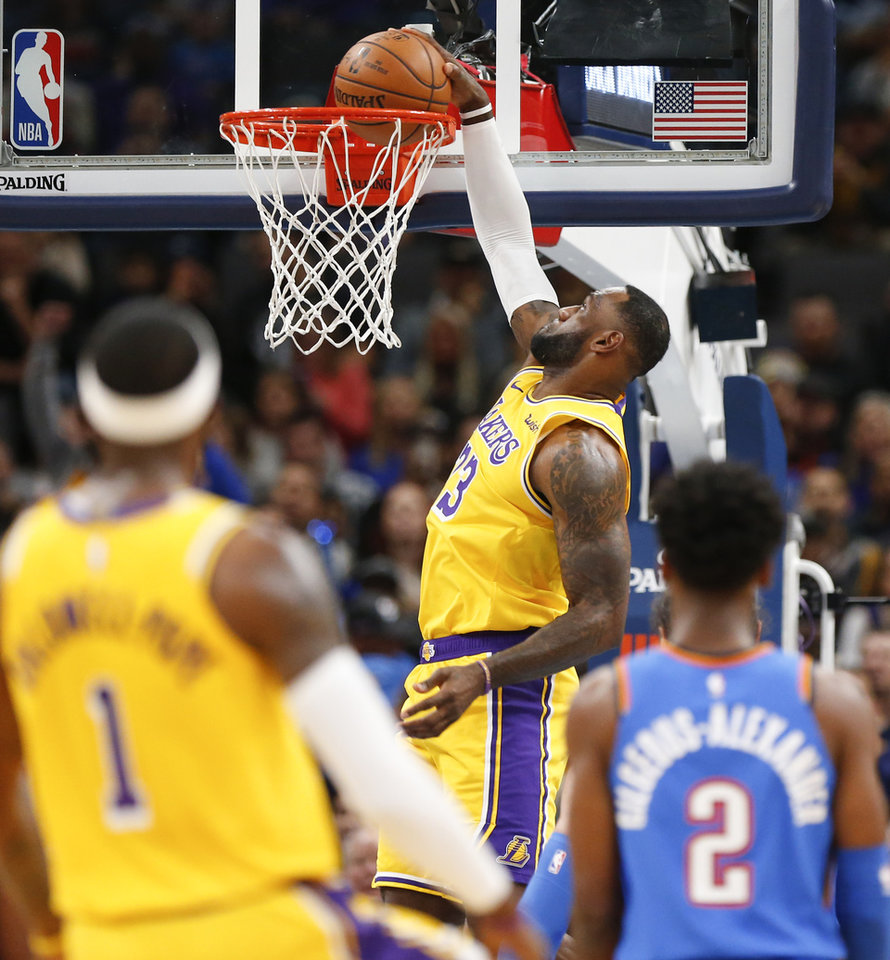 Photo - Los Angeles' LeBron James (23) dunks the ball in the first quarter during an NBA basketball game between the Oklahoma City Thunder and the Los Angeles Lakers at Chesapeake Energy Arena in Oklahoma City, Friday, Nov. 22, 2019. [Nate Billings/The Oklahoman]
