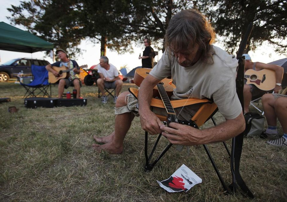Photo -  Jody Thom, of Fayetteville, Ark., replaces his guitar strings near his camp site during the Woody Guthrie Folk Festival in Okemah, Okla., Thursday, July 12, 2012.  Photo by Garett Fisbeck, The Oklahoman