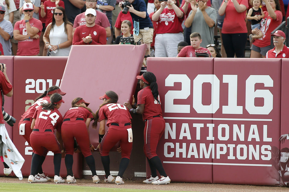 Photo - Oklahoma players take a piece of the outfield wall after winning the second game of the NCAA softball tournament in the Norman Super Regional between the University of Oklahoma (OU) and Northwestern in Norman, Okla., Saturday, May 25, 2019. Oklahoma won 8-0 to send them to the Women's College World Series.[Bryan Terry/The Oklahoman]
